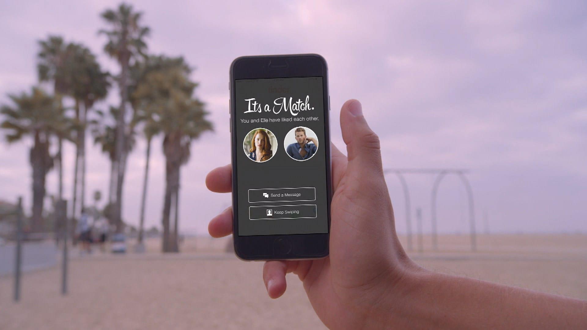Um homem segurando celular com Tinder na mão