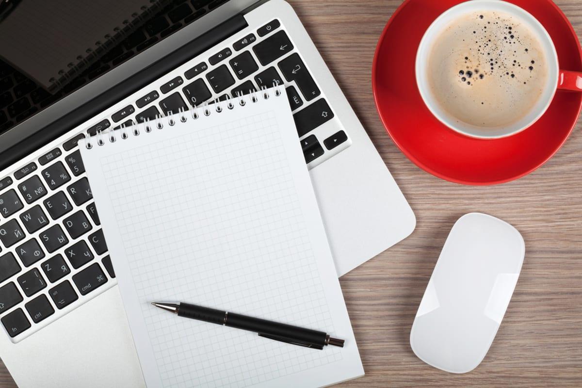 Imagem mostra notebook, bloco de notas e café